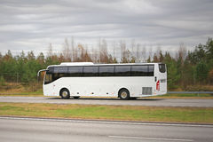 White Coach Bus on Motorway on a Cloudy Day. New white coach bus moves along motorway on a cloudy autumn day Royalty Free Stock Photography