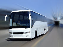White coach in motion. A white tour bus set against a motion blurred background Stock Photos