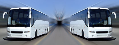 White coaches in motion. Two white tour buses set against a motion blurred background Royalty Free Stock Images