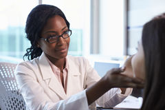 In White Coat Examining医生女性患者在办公室 免版税库存图片