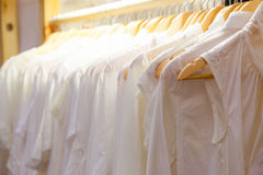White coats hanging on a rack in a row. Royalty Free Stock Image