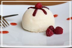 White coconut cake on white plate with raspberry. And fork Royalty Free Stock Photo