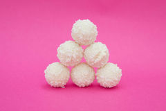 White coconut candies on pink background. Stock Photos