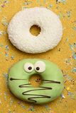 Funny glazed donuts on gold background Stock Photography
