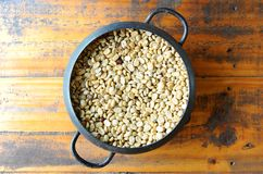 White coffee bean in vintage steel bucket on wooden table royalty free stock photos