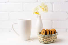 White coffee cappuccino mug mockup with soft yellow orchid in va Stock Image