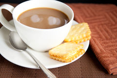 White coffee and cookies. A cup of coffee with cookies and brown kitchen towel stock photos