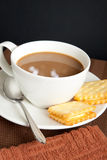 White coffee and cookies. A cup of coffee with cookies and brown kitchen towel stock images