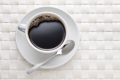 White Coffee Cup Background. A coffee cup full of black coffee with a spoon on a white placemat background royalty free stock photos