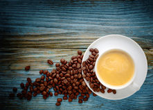 White coffee cup and beans on old wooden background. Stock Photo