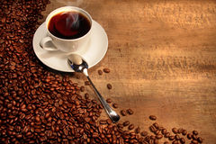 White coffee cup with beans on rustic  table Royalty Free Stock Photo