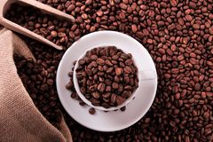 White coffee cup with beans sack and scoop top view royalty free stock photography