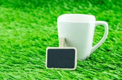 White coffee cup and blackboard clip on grass,Template for addin Stock Images