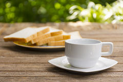 White coffee cup and bread slice on wooden table and nature background. 1 Stock Images