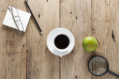 White coffee cup with business objects on old wooden table. Stock Photos