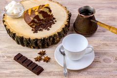 A white coffee cup with a chocolate cake on wooden stump, tea spoon, coffee beans, anise, chocolate bar and bowl with sugar cubes. On a bright wooden table Stock Photography