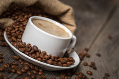 White coffee cup with coffee bag made from burlap sack on wooden table Stock Images