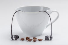 White coffee cup, coffee beans and black headphones on white bac Royalty Free Stock Image