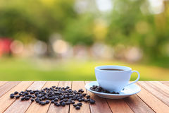 White coffee cup and coffee beans on wood table with blurred bac Stock Photo