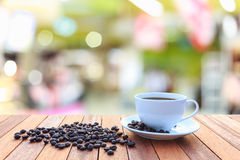 White coffee cup and coffee beans on wood table with blurred bac Royalty Free Stock Image