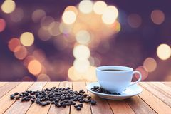 White coffee cup and coffee beans on wood table with blurred bac Stock Photography