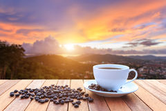 White coffee cup and coffee beans on wood table and view of suns Royalty Free Stock Photography