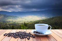 White coffee cup and coffee beans on wood table and view of suns Royalty Free Stock Images