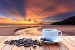 White coffee cup and coffee beans on wood table and view of suns Stock Photos