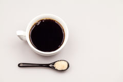 White coffee cup with coffee, plate with coffee beans and black teaspoon with sugar Royalty Free Stock Image