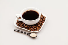 White coffee cup with coffee, plate with coffee beans and black teaspoon with sugar Stock Image
