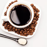 White coffee cup with coffee, plate with coffee beans and black teaspoon with sugar Stock Images