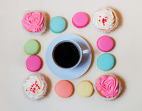 White coffee cup with colorful macaroons and cupcakes Royalty Free Stock Photo