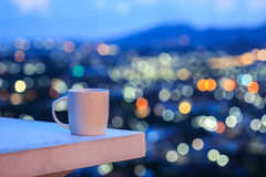 White coffee cup on counter and colorful blur light bokeh of cit Stock Photography