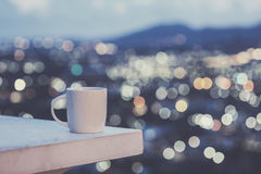 White coffee cup on counter and colorful blur light bokeh of cit Stock Photo