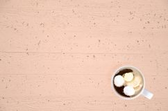White coffee cup with cream on beige concrete table with wood pattern. Top view stock images