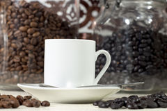 White coffee cup beside different types of roasted coffee beans Stock Photo
