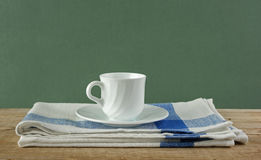 White coffee cup and dishcloth on old wooden table over green ba Royalty Free Stock Photo