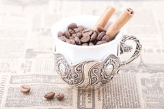 White coffee cup filled with coffee beans on newspaper with cinnamon. White coffee cup filled with coffee beans on old newspaper with cinnamon Royalty Free Stock Photography