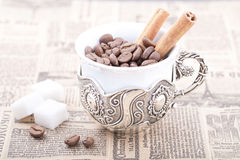 White coffee cup filled with coffee beans on newspaper with cinnamon. White coffee cup filled with coffee beans on old newspaper with cinnamon Stock Images