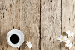 White coffee cup and frangipani flowers on old wooden table back Stock Photos