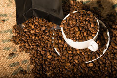 White coffee cup full of beans, surround by more coffee beans an. D a black bag Royalty Free Stock Photos