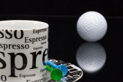 White coffee cup and golf ball Royalty Free Stock Photo