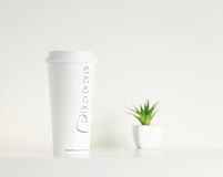 White coffee cup and green potted plant stock photos