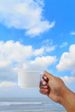 White coffee cup in hand on blue sky background. White coffee cup in hand on beach and blue sky background stock photography