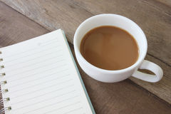 White coffee cup and have empty book on a wooden floor. Stock Photography