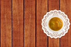 White coffee cup on lace cloth on wooden background Stock Images