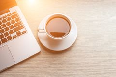 White coffee cup and laptop on wooden table top view stock photo