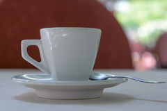 White coffee cup with a little spoon. Closeup of a white coffee cup with a spoon, photographed on a table with white sheet. Photo was taken outdoors on a sunny Royalty Free Stock Photos