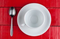 White coffee cup with metal spoon isolated on a red background. Beverage aroma morning breakfast cappuccino hot foam cafe mug energy milk drink vintage latte stock image