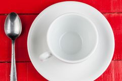 White coffee cup with metal spoon isolated on a red background. Beverage aroma morning breakfast cappuccino hot foam cafe mug energy milk drink vintage latte royalty free stock images